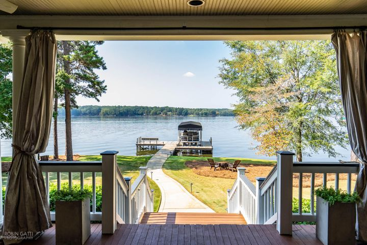 LAKE LIFE at its BEST! This spectacular home sits on a flat, beautifully landscaped lot, right on the water. Big water views don't get any bigger than this w/260 ft of water frontage, max dock 5-6 ft water depth, 7500 lb boat lift w/ tower kit. Open floor plan, new seawall & rip rap, 2 open covered porches, screened in porch easily converts to sunroom. New HVAC units w/Nest thermostats, New roof, billiard room, and upstairs kitchenette, beautiful new outdoor landscape lighting and surround sound speakers throughout. This is a must see for easy living lake life. Conveniently located to Atlanta, Athens, Augusta, and Macon. This property comes with rights to obtain a Reynolds Platinum Membership (access to all golf courses, restaurants, facilities)
