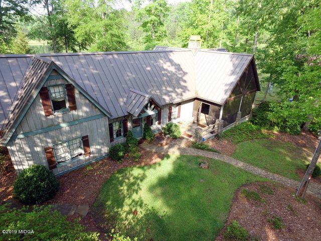 This 3 BR/2 BA beautiful cabin , built by Franco DeMichiel with 1800 sq ft front porch with a large 4-sided fireplace in the center and sits on a 9 acre stocked  lake.   Heart pine flooring and pine paneling. Cooking shed, city water, well, entrance gate. 2 horse pastures, new 3-stable barn and tack room. Approx 1.5 mile road frontage on Reedy Creek Rd and McCowan, approx 1 mile of frontage on Tobesofkee Creek, all road frontage is fence. Approx 150 acres of planted pines.