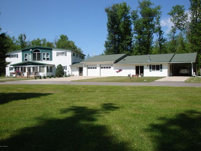 Main building on picture left (currently running as a Bed & Breakfast) with a breezeway leading to a double car garage (currently being used as a fitness room) with a 2 bedroom manager's apartment (currently used as an office in the living room area) and a large carport to the right of it.