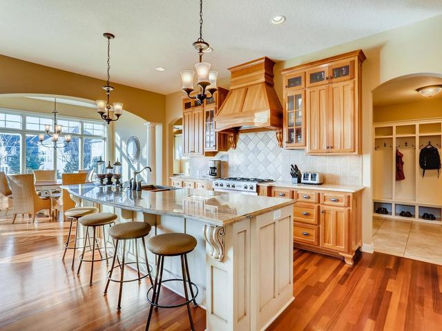 The Main Floor open concept kitchen boasts beautiful hardwood floors, custom cherry cabinetry, and a wonderfully large granite countertop island!
