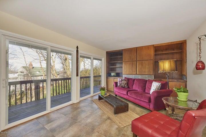 Living Room w/ Wood-Burning Fireplace & Balcony