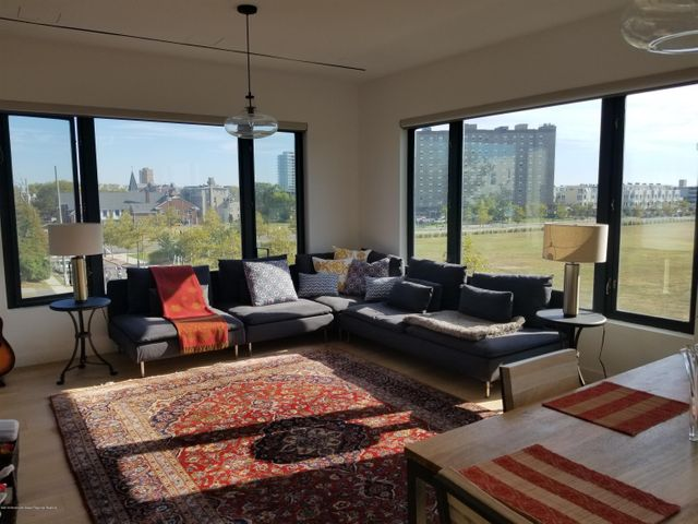 Test drive living in exciting downtown Asbury Park by renting this amazing 6 month Fall/Winter/Summer rental.  Fully furnished this light-filled open concept 1200 square foot plus condo features wrap around windows that boast sweeping ocean views.  Luxury designer finishes abound plus a private covered balcony, wide plank wood floors, entertaining kitchen w/ large island, 2.5 ultra modern bathrooms with one having a large walk in shower & double vanities.   Well located just steps from the center of downtown Asbury & 2 blocks to the beach, boardwalk and Ocean Grove.  Feel like you are on vacation as you venture to near by shops, galleries, bars, restaurants, etc. or enjoy the common roof top patio with fire ring, outside kitchen and dining.  No pets or smokers please.  6 mo summer rate-$30