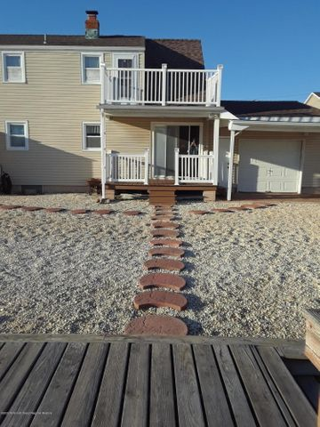Location is what you get with this lovely 4 bedroom 2 bath Cape Cod! Easy access to the Bay and the Ocean, what more can anyone ask for.  This is the perfect getaway to relax enjoy boating and the beautiful beaches of Long Beach Island.  Updated kitchen with granite counter tops and stainless steel appliances. Sliders from the dining room leading to the deck for outdoor dining while relaxing and enjoying views of the lagoon. A cozy wood burning fireplace in the living room for those cool evenings to enjoy what ever you desire. The garage features two doors for easy access to the lagoon for your jet skis or what ever you prefer.  Your own private dock and bulkhead to dock your boat and a sling to lower your jet ski onto the lagoon and enjoy endless hours of fun on the water.
