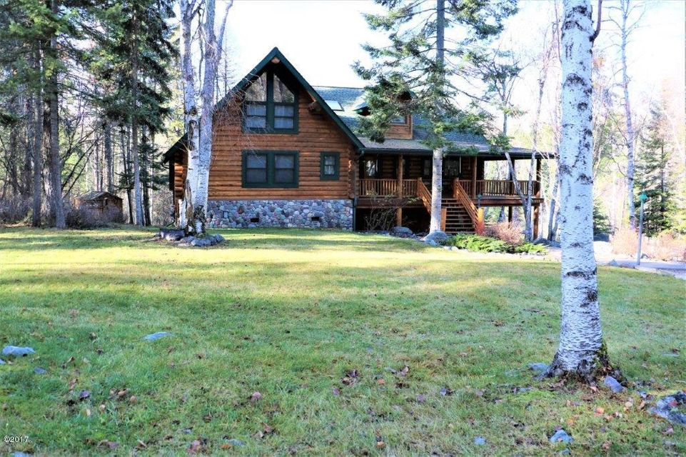 What a peaceful setting for this beautiful log home. Large great room with vaulted ceiling opens up to the 2nd floor game room with bar and pool table.  The dining space is ample for a group of guests and sits just off the bright and wonderful kitchen with new custom granite countertops.  The master suite is on the main floor and has a separate bathtub and tiled shower.  The main floor laundry room is large enough to house a nice office space or be used as an extra guest room.  Upstairs has two bedrooms and a full bath.  The daylight walk-out basement has 2 more bedrooms, a half bath and the double car garage.  Plenty of room for everyone!  The porch wraps around three sides of the home for loafing in or out of the sun at your will.  Your own private Montana Lodge!