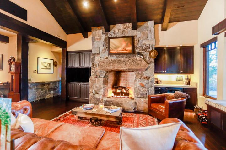 Great room features vaulted ceilings, stone fireplace converted to burn wood and a hidden projection screen theater system.