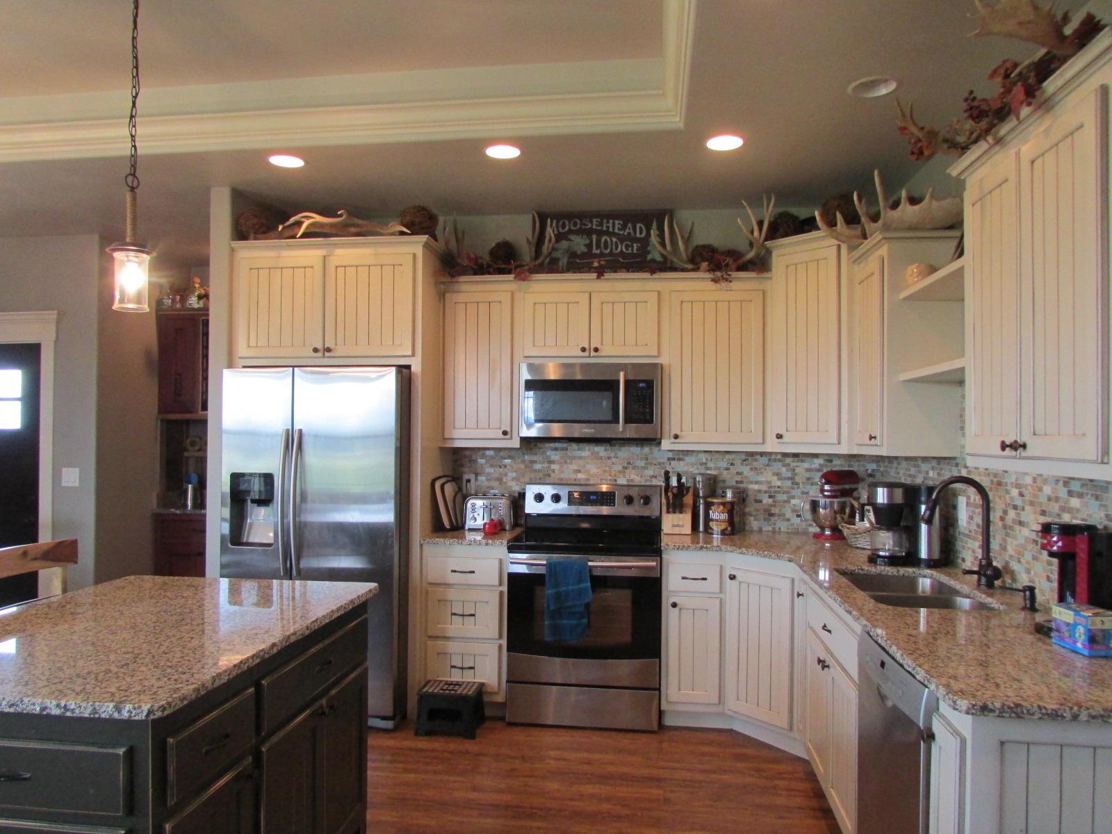 Quartz counters & island, tile backsplash, wood laminate flooring, stainless steel appliances, tray ceiling
