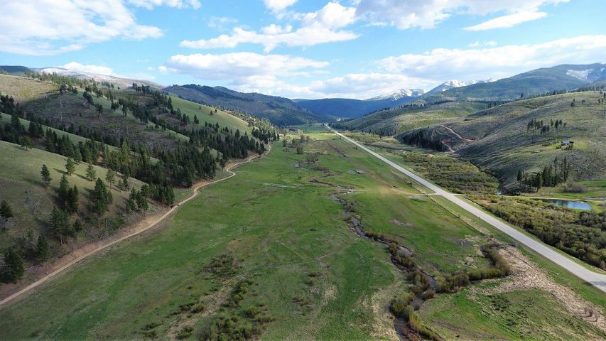 Subject property is on left of photo & gravel rd, property in middle is Public/STATE ground , Camp Creek flows through, excellent trout fishing, Hwy 93 on Right of photo