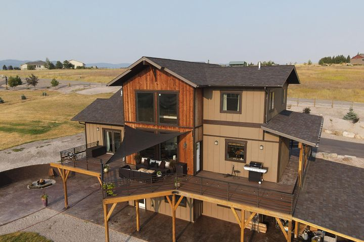 Back view of house with deck and patio, firepit