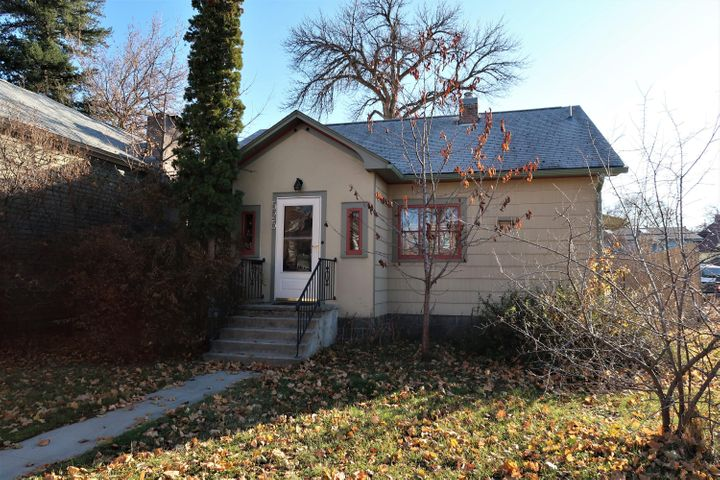 This adorable Riverfront area home offers many possibilities with a 6,370 sq. ft. commercially zoned lot and is within an easy walk or bike ride to all the best that Missoula has to offer.  You'll love the charm and character throughout the main level which includes beautiful hardwood floors and crystal doorknobs and handles.  The living room has been updated with a convenient and cozy gas fireplace with decorative tile surround and wood mantle.  Open to the living room, the eat-in kitchen features great storage with tall cabinetry and a custom floor to ceiling built-in pantry with pull out shelving and additional open shelving.  A full bath with a wall of built-in storage is conveniently located between the two main level bedrooms.  Upstairs you'll find the heated and finished attic space