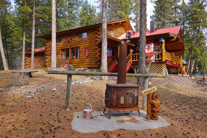Enjoy the western lifestyle in one of the quietest ,most beautiful spots left in the NW ! This property has a rustic and genuine log home,affectionately known as the Red Door Lodge. The property also comes with a 2 bedroom guest cabin,  barn, horse stall, wood shed, a harness shop, an RV used as extra sleeping quarters and a dune buggy to travel the sandy banks of near-by Lake Koocanusa ! It also has a fenced garden and green house for the gardening enthusiast. Property has it's own well and septic system. Property is currently being used as a thriving vacation rental . No covenants and no HOA fees and comes fully finished. The second cabin is currently rented bringing in revenue. This property is turn key and move in ready and is easily accessible being located on a paved county road !
