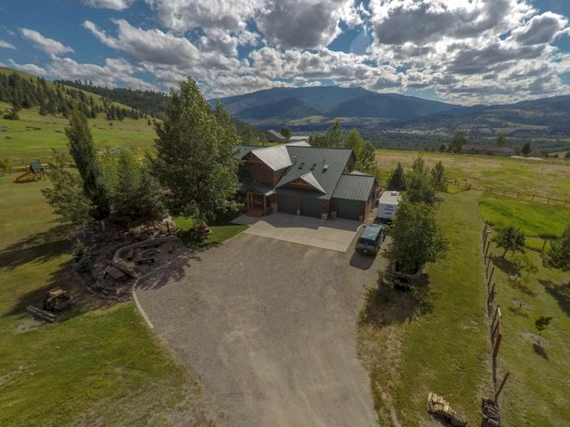 Western Montana Estate with panoramic views of Lolo Peak, Missoula valley, and the Bitterroot, with 6 bedrooms, 4.5 bathrooms, over 6,000 square feet on 10 plus acres set up for horses. Barn and riding arena with entire property fenced. Cedar sided home with log accents; granite counter tops and stainless steel appliances in kitchen (new Kitchenaid double oven) with gas Jenn-air cooktop on island; breakfast bar made of blue pine. Nook off of kitchen with access to spacious walk-in pantry. Great room main living area with massive river rock fireplace and attached dining room; two sets of french doors to expansive wrap around deck with stairs to access side and back yards on both ends. Main floor master with french doors to deck. and newly remodeled master bath with large