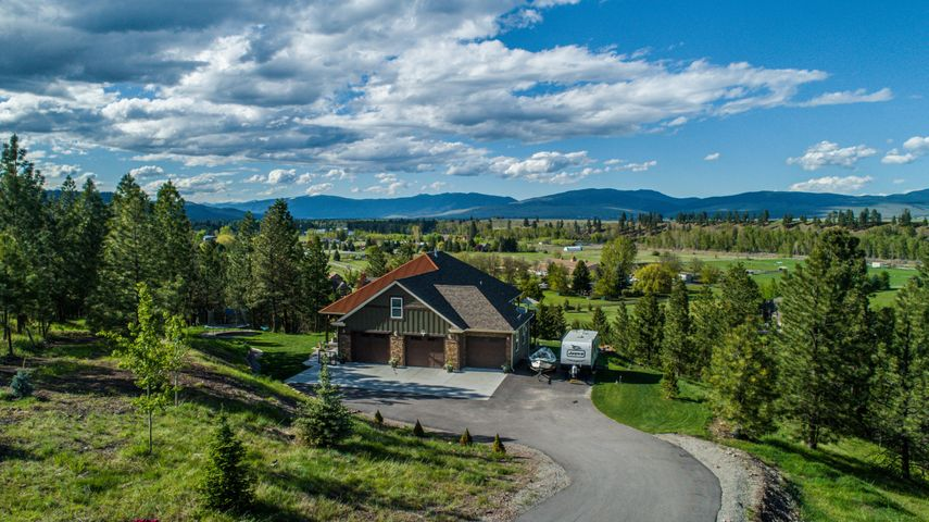 Live the Montana Dream on this majestic, quiet, rare property right off of Big Flat Road. Sipping your morning coffee on the oversized wrap around deck will never be the same. Ever changing mountain views, acreage of beautifully landscaped space and a lot of privacy is the just the beginning. This custom home was born in 2016. When the current owners purchased it, they essentially upgraded the home with new bathrooms, new paint inside and out, new driveway, new custom yard with four custom retaining walls, new Pottery Barn lighting inside & out, new eclectic brick floors and much more. Beautiful wood floors throughout, this home has 5 spacious bedrooms, 4 full bathrooms and is on over 5 acres with newly seeded natural grass. Upgraded plumbing and radiant in floor heating throughout as