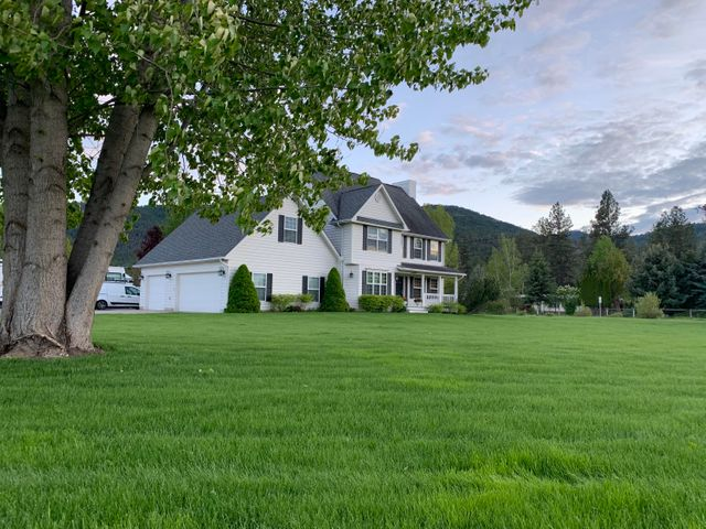 You'll love this two story Colonial Style home located on the prestigious Big Flat area just 2/10's of a mile from the Clark Fork River on 1.22 acres. This 4 bedroom, 2.5 bath 2,708 sq. ft. home offers a large kitchen open to the dining and living room with a custom stone fireplace and custom faux venetian walls. The Mudroom, 1/2 bath and separate laundry are off the kitchen for convenience. There is a formal dining, tv room or office off the foyer. Foyer opens to a half circle staircase with a visible balcony on the second floor. Master bedroom has vaulted ceilings with attached master bath featuring custom tile work, heated tile floor, knotty alder cabinets with granite counter tops and walk in closet.  All 4 bedrooms are large and offer walk in closets.