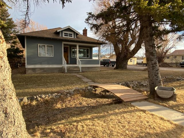 Come home to small town living and a charming older home offering old world style and updates. You'll love the mostly original wood floors and newer laminate in the wide open kitchen. Kitchen also boasts a fir, built-in china cupboard. The living room has a beautiful brick wood burning fireplace and is open to the kitchen. Two bedrooms are one side of the home and the big master on the other. One bedroom has an original built-in dresser. You'll enjoy the fully fenced backyard with a large deck, an enclosed shed and an open shed. The yard has mature landscaping with big old trees and has an irrigation ditch with seasonal water flow in the front. The basement is unfinished, but there is plenty of space for expansion. Call Lynn Kenyon at 406-770-0013 or your real estate professional. Basement houses laundry with washer and dryer included. There is a also a space upstairs for washer and dryer hook ups. Covered front porch. Augusta is a known destination for hunters, fisher people, hikers, tourists and those seeking a true Montana lifestyle. Augusta has restaurants, bars, antique and gifts shops, a grocery, gas station, library, school, churches, motel and more. Rinnai hot water heater. Roof on home has t-lock shingles which seller says are in good condition. Well and city sewer. Augusta is in a flood zone, so lenders will require flood insurance. Seller has a sump pump in the basement.  Buyers to verify all representations to their own satisfaction.
