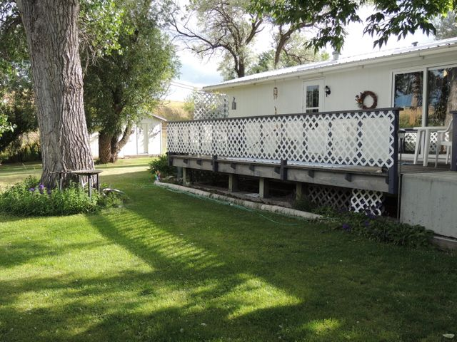 Private, large (1/3 of an acre) fenced yard with many perennials and a cement RV parking pad (24' x 20') come with this 2/2 which includes updated bathrooms, a pantry in the kitchen, newer windows and a master bedroom large enough for a California King-sized bed.  Lots of room in this oversized plumbed/heated 2-car garage plus two sheds and a charming deck offset by a large patio that spans the area between house and garage.  Newer metal roofs, updated plumbing, A/C and lower taxes because this property sits just outside the city limits, but still has city water, with an option to connect to city sewer.  This one is clean, well-cared for and ready for you to move right in.