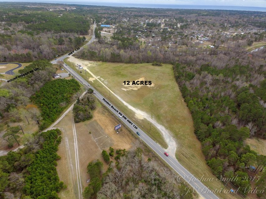 Over 1,100 feet of frontage hwy 130.  INTERSECTION of Holden Beach Rd with Road frontage on Holden Bch Road too. Low density commercial. Perfect location to build strip L shaped shopping center with grocery store as anchor tenant and a convenience/gas store out front with car wash.Also perfect location for a temp.controlled storage facility some spaces large enough for travel RV's and Big Boats.This 12.09 acres has 11 acres of buildable land,pond onsite might be possible to use for storm water run-off with proper permits.DOT has purchased small front corner of property,because they have future plans for stoplight. This property consist of two parcel numbers being parcel 2150000201 (Plat Book Q/309 NC 130) and parcel 2150010003 being 3.26 acres +/- (tract-A1 acres 3.26 ac. Plat 26 pag. 45