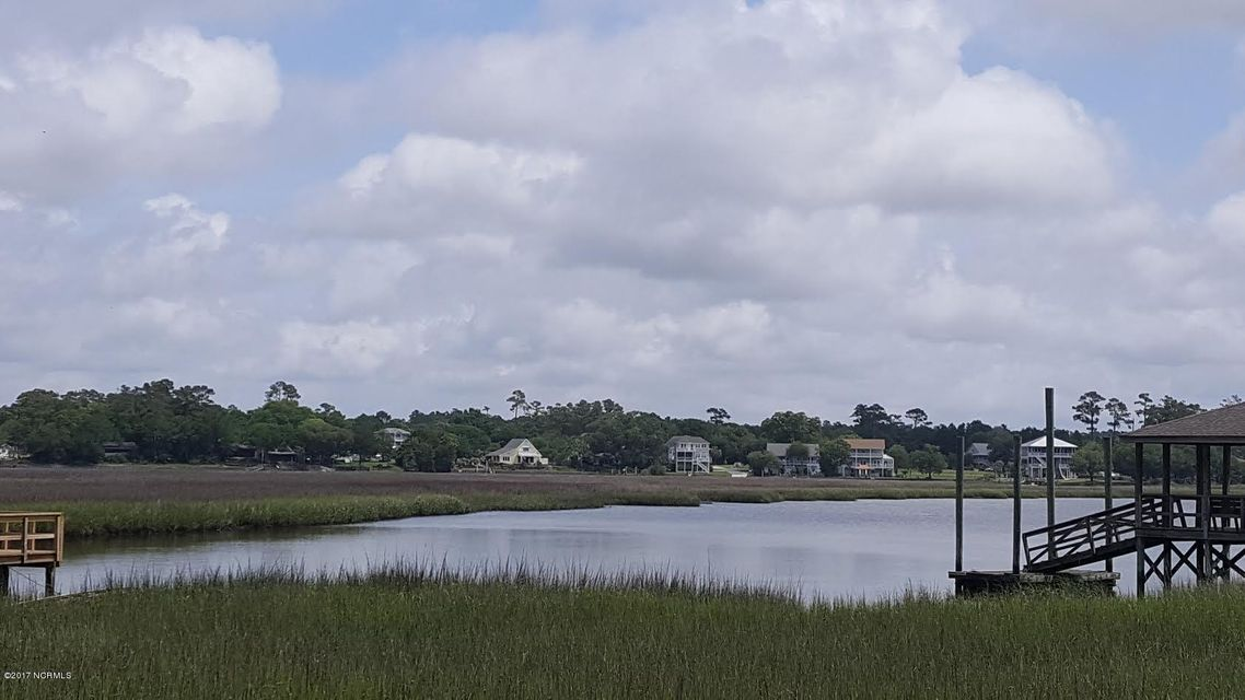 Big Beautiful highly elevated .52 of an acre waterfront and marsh front lot with 3 Bedroom Septic Tank installed. Wonderful saltwater breezes. Click on and view the new Drone virtual Tour to appreciate this waterfront & Marshfront location. With proper CAMA Permit can build pier. This lot next to Riverside POA gate that leads private boat ramp & pier. It is not mandatory to join the Riverside POA, however property owner can voluntarily join for 200.00 year and have access to shallow draft private boat ramp. 5 min. to Holden Beach.