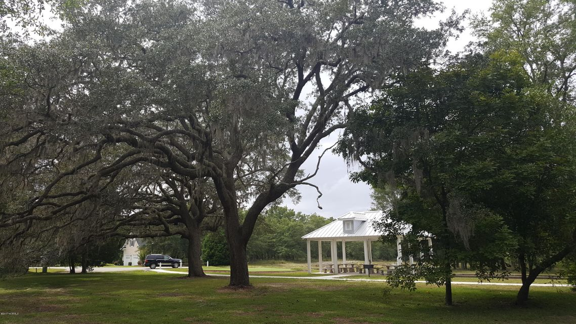 ABSOLUTELY A DROP DEAD GORGEOUS HOMESITE. See all photos to appreciate the view of pond, 500 year old Live Oak Trees, Bocce Ball Court , Gazebo and putting green just a few feet from your front yard, and so very lovely, shaded and SOUTHERN with Spanish Moss dripping from trees and everything. You are only a 10 minute drive to the white sugar fine pristine sands and shores of Holden Beach, a beautiful Family Beach. Golf courses 15 min. away. Gated Community offers big Pool, Clubhouse, many walking trails, tennis/pickle ball, day dock, boat ramp, boat storage, canoe pier. Oyster Harbour is a nature lovers community, very pretty, quiet and an abundance of wildlife. Watch the birds native to the coast, newborn deer in the spring,  squirrels frolicking in the trees, all from your porch or deck.