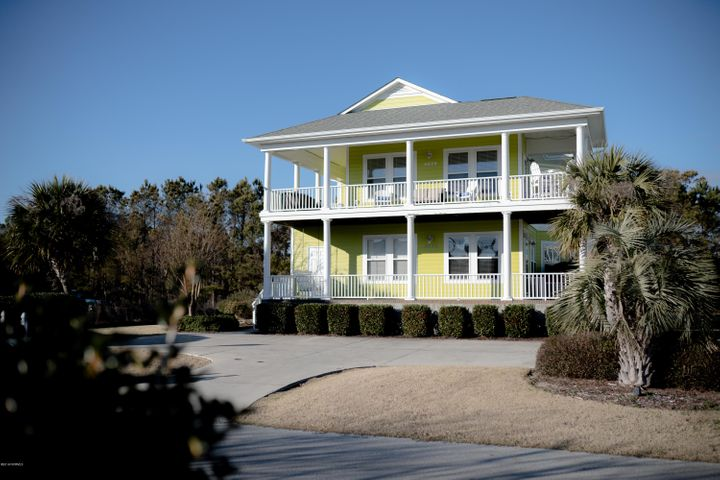 This second floor unit of a spacious up/down duplex overlooking South Harbor Marina offers the delights of coastal living before you even step through the front door.  The wrap around porch which lines the front half of the perimeter offers gorgeous views of the Intracoastal Waterway and is an ideal outdoor living space, with room for furniture on all sides.  The entrance spills directly into a large open floor plan with a living room and dining space lined with several tall windows, enabling you to enjoy waterfront views from the south and east sides of the home.  The kitchen, seated directly behind the dining area, has plenty of work space and a counter height breakfast table which seats four. A wide hallway which begins at the front entrance leads to two bedrooms to the left, with a half bath in between, and then farther down the hall, a full bathroom on the right, with extra shelving and storage space. There are hardwood floors throughout the main living spaces. The master bedroom, which overlooks a private wooded area with no development behind it, houses the second full bath, which has both a tub and stall shower, as well as an oversized  walk in closet with enough room for extra storage furniture or shelving.  The master bedroom also gives access to a private balcony, separate from the wrap around porch at the front of the unit. This home is an ideal coastal getaway or investment property in addition to working perfectly as a primary residence.  Enjoy the convenience of the marina, shopping and restaurants directly across the street, or take a short drive to the Oak Island beaches or historic Downtown Southport.