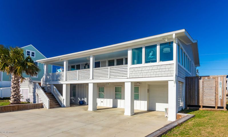 Classic, updated cottage in Atlantic Beach located on a double 3rd row lot that is just steps to the ocean -- filled with the warmth of real wood and plenty of natural light, this beach retreat is the perfect gathering spot for family and friends offering great spaces inside and outside with an elevator for easy access between floors. The large front covered porch opens into the main living areas including the modern kitchen with solid surface counters, a breakfast bar and a formal dining space. The cozy sunroom with a vaulted ceiling is the perfect spot for relaxing and also on this level is the master suite with private bath, a suite-style guest bedroom with a 1/2 bath and another guest bedroom and a full hall bath. The first floor includes a bonus room for an additional guest space or   den, 3 additional flexible use rooms, 1.5 baths and a large laundry/storage room. Outside areas include: 1-car attached garage/storage area, large exterior storage, decking, patio, covered porches and a double outside shower. Great location within walking distance to the AB Circle for restaurants, shopping and more!