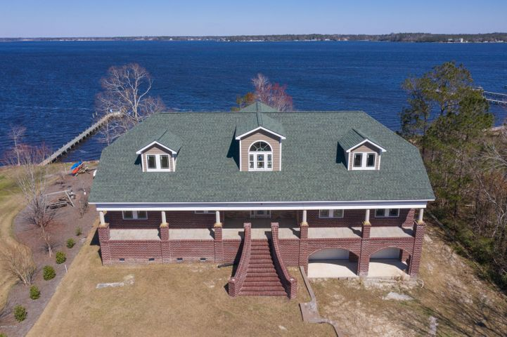 AMAZING WATERFRONT HOME - 1.26 ACRES - 4,700 SF - 175 FEET OF SANDY BEACH ON THE WHITE OAK RIVER WITH A 650 SF BASEMENT. This is your opportunity to customize your beach and waterfront estate home that combines acreage with endless water views and water access to the White Oak River. The lot is designed for a pool, spa and outdoor dining areas. From your own riverfront sandy beach, you can launch a kayak or tie up your wave runner. Install a dock and lift right on the river, and boat just minutes to the ICW and historic downtown Swansboro. The private boat ramp is located just a few lots away. The White Oak Crossing community has tennis courts, private boat ramp, club house and a beautiful pool.  Your home will be located minutes from historic Swansboro where you will enjoy tours of historic homes dating back to the 1700's, weekly summer concerts, restaurants, low-country boil, renowned fritters, sweet-shops, boat tours, dog walking, shops and Swansboro's famous festivals. The home is heavy framed with mechanical components installed. The huge rooms make most design changes possible at this point unlike a completed home that requires the expense of gutting and remodeling. The home is ready for electrical, insulation, drywall, interior and exterior finishes. The 650 SF basement has a block walled room with a vault door.  The room is climate controlled to store the owner's valuables or possibly wine. A valt room is located in the basement which is climate controlled and has a bathroom.  In the three-car garage area, there is a dedicated space for a full house generator, and a spacious workshop. There is cavernous under deck storage under both decks that can house water toys and supplies. The home is designed with Handicap requirements in mind with a three floor elevator, extra wide doorways and halls. Projected cost to complete is available.