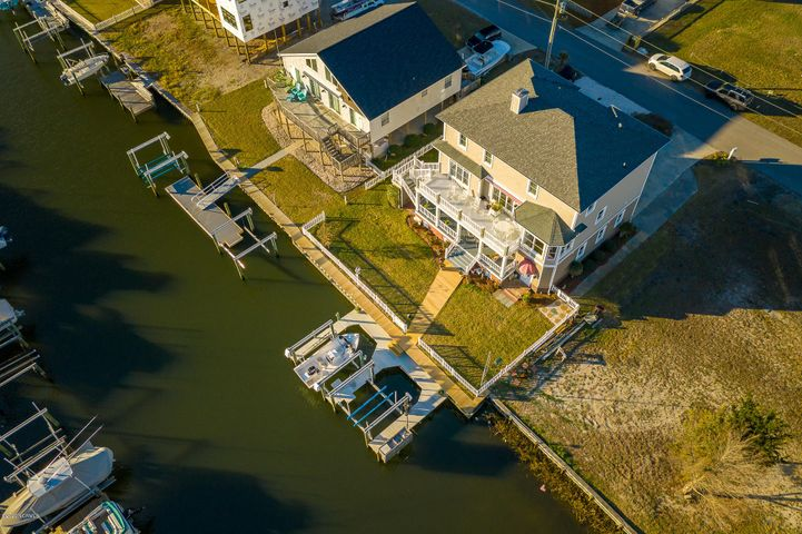 Quality-built, meticulously maintained home on a deep water canal with easy access Bogue Sound and the ICW! Great indoor and outdoor spaces for family and friends to gather or spread out and enjoy living the coastal life (see sketch under documents). Three story home with an elevator to all floors: 1st floor offers a covered entry into the foyer, 2 bonus rooms, 1/2 bath and large recreation room; 2nd floor offers an open kitchen, living and dining area, large pantry, master suite with en-suite bath, laundry room with 1/2 bath; 3rd floor offers two guest bedrooms, an office and a flexible use room. One bedroom on the 3rd floor is rough-plumbed for a future full bath - this space could be a second master suite. Furnishings are negotiable separately except for the exclusions list.