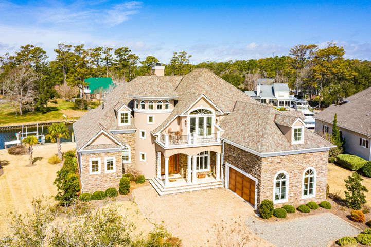 Custom Eddie Cameron Construction home designed by architect Dan Sater with 101' floating dock and additional  16,000 lb. boat lift on protected deep water tucked just off Bogue Sound.  Appraisal in hand for $1,950,000.  A truly unique home for our area - attention to detail and craftsmanship at every turn! This light-filled floor plan offers a smart layout with water views everywhere. The great room includes a waterfront den with gas fireplace, informal dining and chef's kitchen (Wolf: range, oven, microwave, warming drawer and subzero refrigerator) and gorgeous cabinetry and countertops that extend for an eat-in bar.  Adjacent to the kitchen and framed from the entrance by an arched ceiling is a fabulous wetbar with additional refrigeration and beautiful cabinetry. The dining room with coffered ceiling opens to the living room with spectacular 22' ceilings and a double sided gas fireplace shared with a cozy water-side office.  The first floor master suite is expansive and luxurious, with a huge bath, separate walk-in closets and doors leading to the gorgeous Cumaru (Brazilian Teak) decking overlooking the water.  A half bath for guests and a separate laundry room are situated near the door to the true two car garage, with additional room for storage.  There are two stairwells to reach the upstairs level - one from the great room and the other a rounded stair case at the entrance.   The workmanship will take your breath away!  Upstairs includes 4 bedrooms and 3 full baths, with one bedroom currently used as a bonus room.  An upstairs living area with wetbar and small refrigerator and dishwasher opens to the formal living area below, creating separate spaces, with an open, inviting feel.  Unsurpassed construction quality and room for multiple boats in a protected location. This home is truly one of a kind!