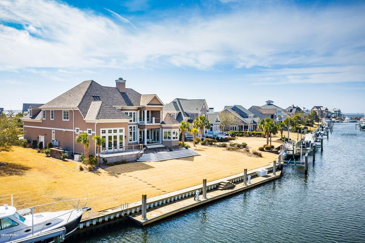 Custom Eddie Cameron Construction home designed by architect Dan Sater with 101' floating dock and additional  16,000 lb. boat lift on protected deep water tucked just off Bogue Sound.  Appraisal in hand for $1,950,000.  A truly unique home for our area - attention to detail and craftsmanship at every turn! This light-filled floor plan offers a smart layout with water views everywhere. The great room includes a waterfront den with gas fireplace, informal dining and chef's kitchen (Wolf: range, oven, microwave, warming drawer and subzero refrigerator) and gorgeous cabinetry and countertops that extend for an eat-in bar.  Adjacent to the kitchen and framed from the entrance by an arched ceiling is a fabulous wetbar with additional refrigeration and beautiful cabinetry. The dining room with coffered ceiling opens to the living room with spectacular 22' ceilings and a double sided gas fireplace shared with a cozy water-side office.  The first floor master suite is expansive and luxurious, with a huge bath, separate walk-in closets and doors leading to the gorgeous Cumaru (Brazilian Teak) decking overlooking the water.  A half bath for guests and a separate laundry room are situated near the door to the true two car garage, with additional room for storage.  There are two stairwells to reach the upstairs level - one from the great room and the other a rounded stair case at the entrance.   The workmanship will take your breath away!  Upstairs includes 4 bedrooms and 3 full baths, with one bedroom currently used as a bonus room.  An upstairs living area with wetbar and small refrigerator and dishwasher opens to the formal living area below, creating separate spaces, with an open, inviting feel.  Unsurpassed construction quality and room for multiple boats in a protected location. This home is truly one of a kind! NOTE: Dryvit was used as one of the exterior finishes, as well as, stone.
