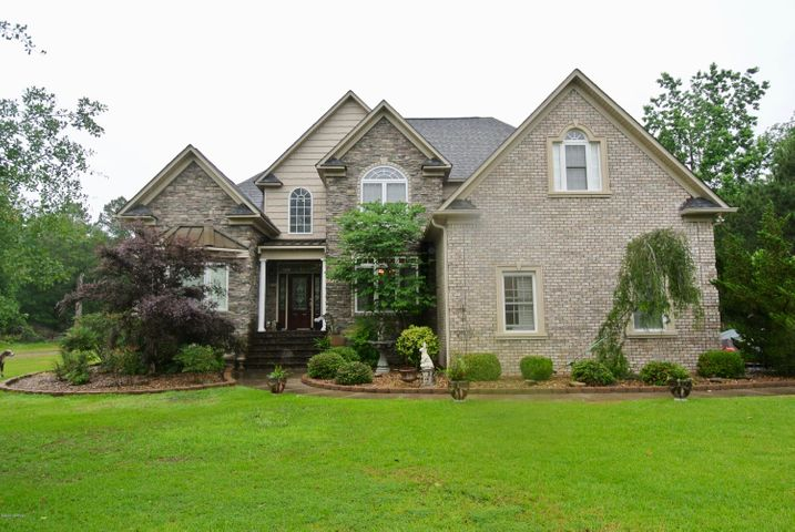 2007 Winner of the Parade of Homes Tour. This stunning custom built home sits on 0.84 acres of land in Quail Woods Subdivision. Step into the foyer with 20 foot ceiling, formal dining room, massive living room w/20 foot ceiling & beautiful stone see through gas log fireplace that connects into the cozy Carolina room. Living room is overlooked by the oversized kitchen area. Kitchen has granite counter tops, GE appliances, long bar area to entertain & large eat-in area w/coffer ceiling. First floor master bedroom has crown molding & tray ceiling. Master bathroom offers split double vanities, large wall-in tile shower, jetted tub, walk-in closet. Downstairs also has additional bedroom, full bathroom & laundry room w/soaking tub. Upstairs offers 2 sizable bedrooms that share a full bathroom w/double vanities in the hallway. Has massive 29'6 by 12'4 finished room over the garage. Has attached 2 car garage, double sided fence in backyard, 15'8 by 19'6 stamped concrete patio w/wrought iron rail & detached 2 storage barn at rear of the lot. House is within 10 minute drive from Downtown New Bern & offers no city taxes!