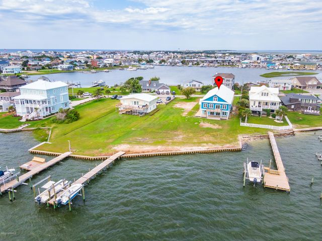Beautifully updated home on TWO soundfront lots ready for a new buyer to enjoy! Gorgeous waterviews and easy access to Bogue Sound and the ICW for recreational and sportfishing waters -- spend a day at Cape Lookout or cruise to your favorite waterfront restaurant all from your backyard boat dock with 2 lifts (5,000 lb & 13,000 lb - with new motors). Newly remodeled home by Sammy Ballou offers a spacious main living area with an open concept living, dining and kitchen on the first floor all with waterviews! The second floor features the master bedroom with en-suite master bath, 3 additional suite-style bedrooms/baths and a flexible use room with a bath plus a large bonus family or media room on this level. Outdoor spaces include: open and covered decking, a 3-car attached garage, new bulkhead and boat dock with 2 lifts. Your coastal getaway in Atlantic Beach is move-in ready!