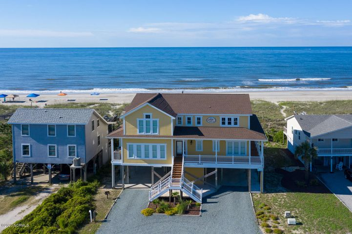 Beautiful ocean front property large enough for entertaining several families at once. Built-in fenced pool and hot tub surrounded by a deck with private walkway leading to beach front, foot shower located next to pool and full outdoor shower next to outdoor storage to store all your water toys. First floor front foyer has tiled floors, that opens to media room surrounded by 8 good sized carpeted bedrooms/full bathrooms, laundry room, leading to deck and pool/hot tub area. Second floor opens from stair well or elevator to a grand living area with hardwood floors, gas-log fire place and built-ins, formal dining/glass table that seats 10, granite breakfast bar, large open kitchen that will accommodate several cooks, with double refrigerators,  large pantry. This floor is surrounded with windows on all sides, two master suites with bathrooms and a bonus sitting/office room that over looks the ocean. Living space leads to upper deck with panoramic ocean view. Double car driveway, large 2 car+ carport with entrance to elevator or stairwell. All furniture and appliances are included in purchase. This is a great investment property currently listed as vacation rental with potential annual income of $150,000+.