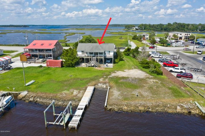 Deep water lot with 130' directly on the Intracoastal Waterway has private boat ramp and dock with lift. Gorgeous views! Modular home on property has 3 bedrooms and 2 baths, but was badly damaged inside from hurricane Florence and is offered as-is. Mostly ceiling damage and mold. No flooding except in the workshop on ground level.  The lot alone is worth the price! Large decks front and back--street side has views of the White Oak River and the water side has grand views of the ICW and Bogue Sound.  Great fishing off your dock or venture out Bogue Inlet to the ocean for the big ones. Take your boat and enjoy shelling, fishing or just explore the many islands and quiet time away from it all! Repair or replace this to make it your little piece of paradise!