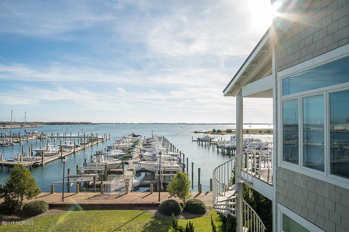 Rarely available front, soundview unit in Atlantic Harbour which conveys with Boat Slip #61 and a new 20,000 lb lift in the marina at Dockside Yacht Club (boat slip is conveyed by certificate). Gorgeous waterviews of Sugarloaf Island and Bogue Sound -- walking distance to restaurants, shopping, parks and the downtown Morehead City Waterfront area. Spacious living area with waterviews and vaulted ceiling, kitchen and dining area overlooking the water, elevator to all floors, master suite and two guest bedrooms. Outdoor spaces include: front entry stoop, covered and open soundview decking, a ground level patio, exterior storage closet and a one-car garage with extra storage space. The coastal lifestyle awaits!