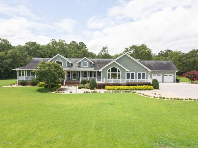 This coastal NC equestrian estate is exquisite with its 7 stall barn, multiple pastures, detached 3 car garage, 60' of enclosed RV parking, & a winding private drive that gives you a sense of arrival to this stunning property. Incredible grounds with over 64 acres total including the home, barn, pastures, and multiple garages/outbuildings. This custom home features 4 bedrooms, 3 baths, and all one story living with enough room to spread out over the 4097 HSF of living area. Spacious owners suite with trey ceiling, built ins, & french doors leading to the spa-like bathroom, complete with oversized jetted tub with waterfall filling feature, in addition to the walk in shower. Luxury appliances in the centrally located kitchen include a double dishwasher, Wolf gas wall oven, & Wolf gas stove. A 350 gallon, owned, underground propane storage tank serves the kitchen appliances, tankless water heater, and fireplace. Above the garage is a climate controlled storage area with walk in attic access. The 3 car detached workshop/garage is climate controlled for storage of personal items or maybe your classic car collection. The Horse Barn is 40' x 62', insulated, includes 7 stalls, a kitchen, bathroom, and lean to storage along the side of the building.  If you have 4 wheelers, RVs, boats, or other toys, you have plenty of space to store them out of the elements in the RV garage. Two separate wells serve to irrigate the grounds and provide water to the pasture, but the house is connected to county water. If you like to entertain, the pavilion by the pond is the place to park a grill and have a gathering! Cast a line into the private pond and maybe catch a bass, bream, or bluegill!  Don't worry about power outages, there is a whole home generator that runs everything in the event of power loss! None of this property is in a Special Flood Hazard area, so no flood insurance is required. Take the 3D Tour or call for an appointment to see this one of a kind property today!