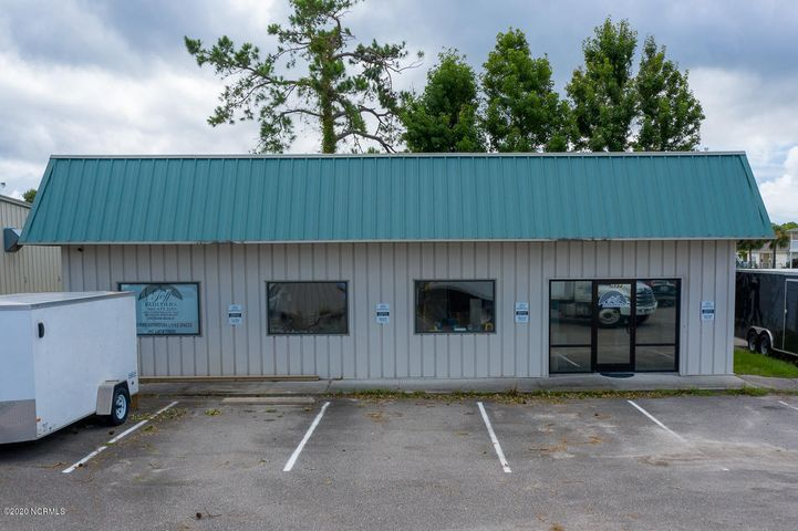 Commercial building in convenient location right on Long Beach Rd between Southport & Oak Island. Total of 2000SF with over 250SF of office space, and the rest for warehouse/storage or multi-use. Offers one car garage bay door, and large windows for plenty of light inside. Currently being used as a custom cabinet shop, but the possibilities are endless.