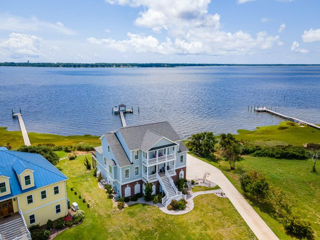 Custom waterfront home of 4,400 square feet built by Streamline Developers offering amazing waterviews and a boat dock with lift (6,000 lbs) at your backdoor! Coastal living on a quiet cul-de-sac setting makes a perfect retreat to call home. Quality features such as: hickory flooring on the main level; a gourmet kitchen with granite counters and stainless steel appliances; two master suites; a media room with a built-in bar; please see the special features sheet under documents for more details. The first floor offers the recreation/media room and a full bathroom. The main living area on the second floor features: entrance foyer; the gorgeous custom kitchen; formal dining space; spacious sun room and living area with a fireplace; the master suite with private bath; laundry area and 1/2 bath for guest. The top floor on the third floor offers 3 additional bedrooms one which could be used as a top floor master with en-suite bath and two guest bedrooms with a hall bath. 3-Car-Garage is oversized (1234 SF) with plenty of room for a workshop or tackle room. Outdoor spaces include: outdoor shower, hot tub, dock with boat lift, large concrete patio, open and covered decking.