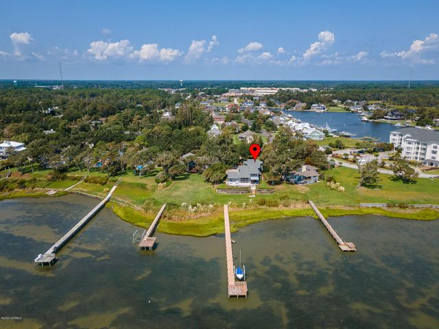Soundfront custom home on a large private lot featuring incredible water views and luxury updates. This home conveys with an onsite pier/dock, as well as Boat Slip A-22 in the Spooners Creek Marina! Livable, easy flowing floor plan with gorgeous light-filled spaces overlooking Bogue Sound. Open concept kitchen, dining and living areas with a fireplace and wet-bar; first floor sound front master suite with spacious bath. Kitchen updated with granite counters and stainless steel appliances. First floor also features a large family den, 1/2 bath and bonus room with a full bath. The second floor features two additional suite-style guest bedrooms/bath, sitting areas and two additional bonus/flexible use rooms for a home office, hobby room or den. Outdoor spaces include: new on-site pier/dock/boat lift, a front entry stoop, an oversized attached 2-car garage, outside shower area, patio, exterior storage and extensive waterside decking.