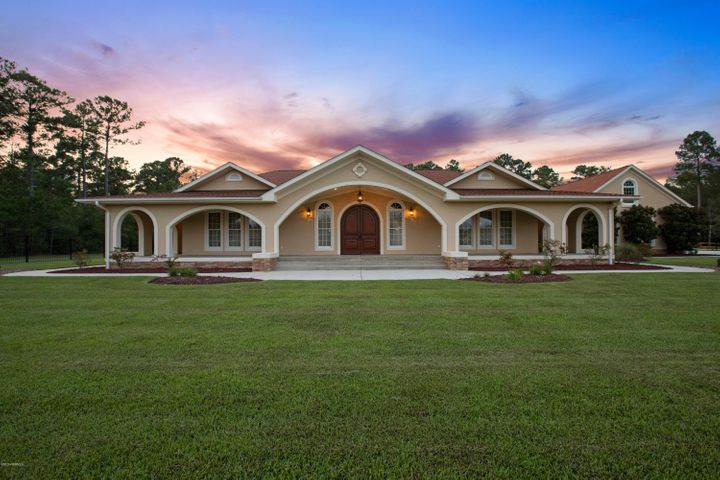 Unique, Custom, exquisite Mediterranean Style home on over 3 acres acres just outside the Jacksonville City Limits! Beautifully maintained gated courtyard home with a saltwater pool, greenhouse and well for the irrigation system within the gates! Conveniently located outside the city limits of Jacksonville. The graceful arches welcome you to make memories in this 4 Bedroom 3.5 Bathroom home. The East Wing features the expansive owner's retreat and the West Wing has an in-law en suite, guest en suite, additional bedroom and media/flex room. This private 3 acre Oasis is artfully designed for ''Family Retreat Living'' with a balance of comfort, luxury and timeless style. The well appointed, gourmet kitchen is designed with form and function to complete the modern chef's dream! The 10ft ceilings accommodate the tiered Custom Cabinetry and there is an oversized pantry with plenty of storage options. The 4 burner/grill and flat top counter gas range is complete with a pot filler faucet! The prep island features a sink, Wolf transitional steamer module and a Sub-Zero under-counter beverage and refrigerator drawers. There is an additional island with a convection and traditional oven. Mexican Travertine tile on the floors and back splash with custom accents. The dining area has a lighted, built in corner cabinet and a double sided gas log fireplace. The Great Room is the focal point of the home. The main entrance is stunning! Double arched front doors are flanked by full view arched windows and the Cathedral Ceiling highlights the courtyard view and the salt water pool. There is an office alcove to the left with a separate entrance onto the wrap around 8ft wide covered terrace. The U shape design centered around the courtyard provides indoor/outdoor living with full view doors and windows filling the rooms with natural light. The owner's retreat on the right continues the exceptional quality. Boutique style custom cabinetry in the walk in closet. The master bathroom  is spa