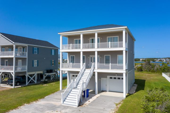 This is a rare opportunity to own a 5 bedroom home with unobstructed views of the ocean and with a dock with 2 1500 lb. jet ski lifts.  The 3 stop elevator makes getting up and down easy.  Wake up in the morning and watch the sunrise over the Atlantic ocean.  Then, go the back of the home and watch the sunset over the ICW and marsh lands.  Four decks run the length of the home, two on the ocean side and two on the ICW side.  All 5 bedrooms have direct access to the ocean views or sound/ICW views from your private deck access.  The 4 bedrooms on the first floor share 2 jack-n-jill bathrooms.  The top floor master suite is off the living room and features a large bathroom and private ocean view access.   There is a bonus room over the living room on the 3rd floor.  Did I mention the hot tub and that the beach access is just across the street?  Also, each floor has a washer and dryer. Heat pumps are almost brand new.  The lot is over 3/4 of an acre.  This property has not been a rental.