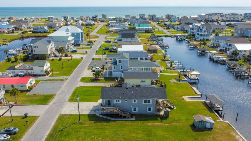 DON'T MISS THE VIRTUAL TOUR and/or Drone Video of the properties surroundings.  With its oversized covered balconies ready for dining, entertaining or just soaking in the beautiful views of the ICW. Everyone will enjoy fishing, paddle boarding, kayaking, from your own dock, right out your backdoor. The interior has been remodeled and was not a rental unit. A delightful open kitchen with granite counters, granite backsplash, stainless upgraded appliances, double ovens, reset lighting and more. With its open floor plan the living space has hardwood floors and beachy colors freshly painted throughout.  A two car garage and additional covered living space on the ground level adds plenty of room for vehicles, beach toys, fishing rods, SUP and even your golf cart. Great as a primary residence or 2nd home for easy, low maintenance living and a dream for passionate boaters.