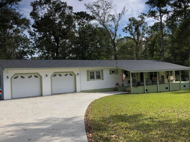 Hunting. Fishing. Loving every day!  This one-of-a-kind, well-maintained property is close to everything while offering peaceful privacy and space we all are seeking. Nestled on a corner lot with nearly 2-acres, this property is in the perfect location--close to Hwy 172 and the back gate to Camp LeJeune, to a short drive to area beaches and the ICW. This home is comprised of over 1,500 heated square feet with 3-bedroom and 2-full baths, a cozy family room with a relaxing sunroom off the back. The property offers a large covered front porch to enjoy the quiet outdoors and the horses across the road. The features of this property are unique, with a large amount of storage space. Some of the features include an attached double car garage, rear detached workshop and shelters, a camper/RV connection, and a large concrete driveway for plenty of parking.  No HOA fees, No City Taxes! New roof! Call or text today to schedule your private showing!