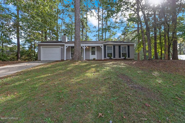A tree adorned corner lot perched on top of a hill and in a cul-de-sac. 3 bedroom home boast ceramic tile, new paint throughout and new carpet in the bedrooms. 1 XL car garage. Weather is getting chilly and it will be time to enjoy a fire in this beautiful wood burning fireplace!  5 minutes from the camp LeJeune main gate. Walking distance to Northeast Creek Park playgrounds, splash pad, nature trails, ball parks, frisbee golf and boat ramp.