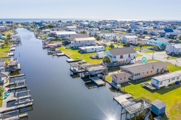 Completely furnished canal home with a Sunbird  boat with only 130 hours. Sitting on the lift, (motor replaced within the last 5 years) and also includes the trailer could be negotiated. This is not your ordinary doublewide. With vaulted ceilings and spacious closets, a GRANDFATHERED sun deck above the boat lift. A new roof in 2019 and HVAC only 6 years old. A florida room that boasts 312 square feet that may be used year round as well as a exterior building wired and plumbed ready to be transformed into your outdoor entertainment kitchen or ''wahoo'' shed.Decisions, decisions...beach day? or boating day? with only steps away from the beach and a boat lift in your backyard, the hardest decision you may have to make is how to spend your day.  This little gem on the canal could be the perfect escape during quarantine or the perfect location for your forever home.