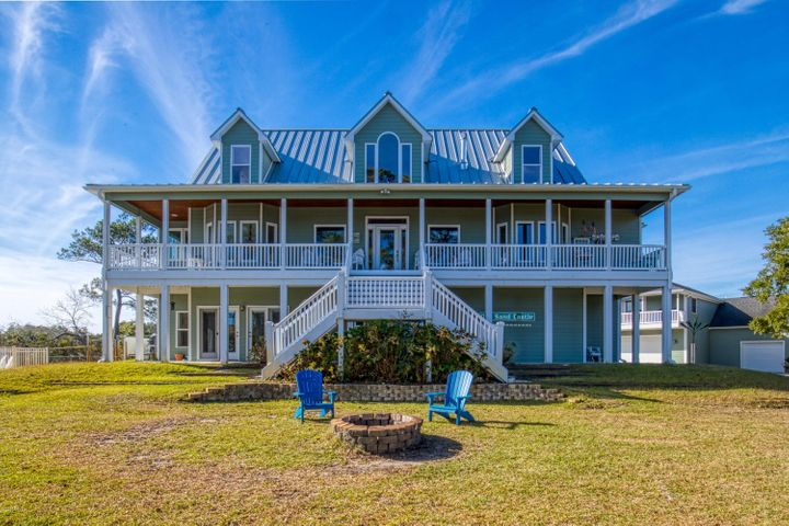 Located in a small coastal fishing village across the bridge from the beautiful beaches of Topsail Island, with the convenience of larger cities Jacksonville and Wilmington nearby. Fully updated Waterfront home sits on 1.79 acres, has 3 separate self-contained living spaces. Plenty of large windows /French doors invite the breathtaking panoramic views into this expansive luxury living space. Magnificent views of the Intracoastal Waterway, Chadwick Bay, Fullard Creek and Biglings Creek from every window and porch of this lovely home. 5078 sq. ft. of total living space, including 3 kitchens and 2 laundry rooms 5 bed/4 bath plus 2 half baths Dedicated office plus small multi-purpose room Located on a quiet private road, on its own peninsula with 763' of Waterfront.  Possibility to sub-divide into multiple lots Luxury plank flooring and ceramic tile throughout entire home Modern gourmet kitchen w/ Stainless Steel appliances, Carrera marble countertops, custom cabinetry, Wolf 60'' dual fuel 6 burner range w/ double griddle cooktop/double ovens, commercial grade hood, XL built in refrigerator and freezer, farmhouse sink, huge island Multiple large porches and balconies w/ breathtaking views Private dock on deep water access w/ 2 covered boat lifts 2.5 car attached garage 6 car detached garage complete with workshop and 800 sq ft walk-up storage attic 1045 sq. ft. guest house above detached garage w/ kitchen, bath, bedroom and spacious living space Inground salt water pool, custom pool cover, solar heating system, hot tub, all completely fenced in Outdoor shower Whole house generator 500 gallon underground propane tank Solar panels help reduce electric bill Tankless water heater Metal standing seam roof Multi-zone sprinkler system supplied by your own well Fenced dog yard A spacious Mother In-Law suite on ground floor with separate entrance, full kitchen, full bath, laundry/mudroom