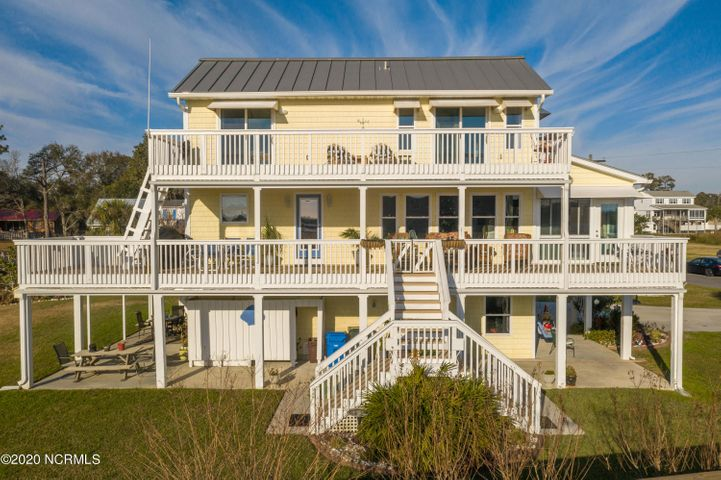 Gorgeous views all around from this deep water canal front home in Cape Carteret.  Three bedrooms, 3.5 baths, beautiful 10 foot wide decks on both levels to enjoy the views of the intercoastal waterway and the Emerald Isle bridge.  Open concept living room, dining and updated kitchen, master bedroom on first floor as well as a closed in porch to enjoy year round.  Upstairs, you will find 2 large bedrooms, both opening to upper deck, full bath and an office.  Home includes 2 storage areas, full hook up for an RV and a pad, private dock with fish cleaning station.  Finished lower level offers a 750 square foot (included in total sqft) rec space and full bath.  This lovely home in Cape Carteret must be seen to truly appreciate.