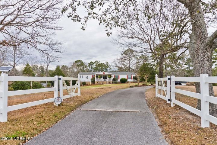 If you are looking for a unique  mini farm on the water, just 10 minutes from Emerald Isle, this is it!! Triplewide on deep water with jet ski lift and dock, on over 3 acres across from White Oak Bluffs in Hadnot Creek. 3 bedrooms, plus office, 2 full baths w/garden tub in master, gas log fireplace, beautiful large deck (942 sq ft) sitting high overlooking Hadnot Creek which leads to the White Oak River and a short ride to the Intracoastal waterway! Gazebo with cooking station on deck. There is Living and Dining Room, Den, Kitchen, Sun Room, Laundry Room.  Wood Floors, Carpet in bedrooms and walk-in closets.Nicely landscaped w/really nice white vinyl fence enclosing the property with a security gate.  420 sq ft Barn and 3 metal carports for equipment,  coy pond, greenhouse with shelving, outside hot and cold shower, workshop. New roof 2015. New septic 2014.  In addition to deep well dug in 2017,  there is a shallow well without a motor. The property is on two lots and one could be sold. Vestor Security System can be transferred.   180 sq ft front porch.  Also there is not an HOA in Hadnot Creek West and an attorney has said that the covenants regarding animals are not enforceable.