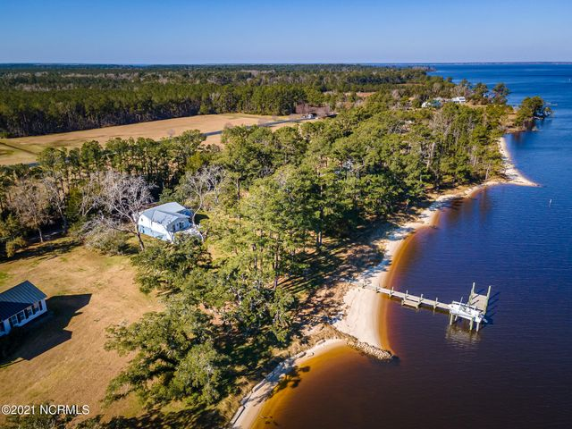 Charming coastal cottage on Adams Creek with awesome views of the water and the ICW! Easy water access with your own pier, dock and boat lift (10,000 lbs) for recreational boating and a sandy beach for relaxing in the sun. The spacious living area opens onto a large waterview deck for extending the living space, there is also a dedicated dining area near the updated kitchen. The master bedroom offers a private bath and there are two additional guest bedrooms, another full bath, laundry area and a 1/2 bath near the kitchen. The ground level offers additional areas (not included in the GLA) such as a huge workshop of 534 sf, a recreation room with 1/2 bath of 203 sf and a home office space of 175 sf. Plus a two-car built-in garage, carport area and an outside shower. This coastal home is ready for a new buyer to enjoy!