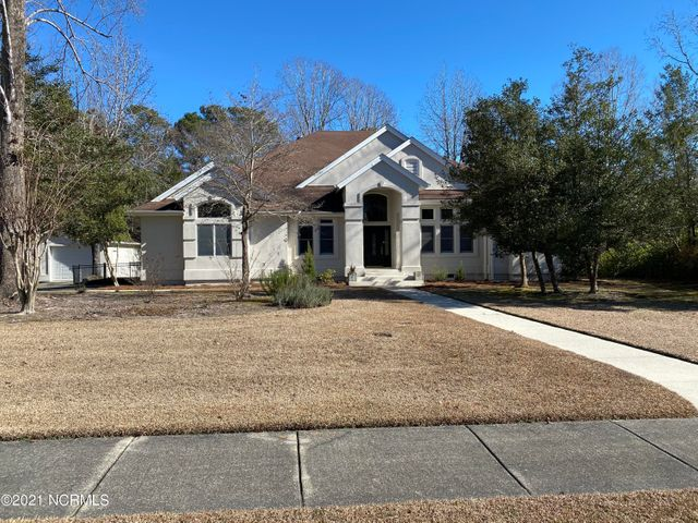 Extraordinarily well maintained executive style home in one of Jacksonville's most prestigious communities! Wonderfully open split bedroom floor plan with huge windows that provide tons of light, and an opportunity to overlook a very spacious almost one acre lot. Many upgrades include 18' ceilings in all living areas, vaulted ceilings, recessed lights, flat ceilings, custom window treatments, an alarm system and more... Enter through a covered front porch to a formal hardwood foyer. To the right is the formal Living room, open to a raised formal Dining room with custom chandelier and decorative columns that provide additional definition and class to the space! To the left is a study, separated from the foyer with a glass paneled door. It has built in cabinets and bookshelves, a custom