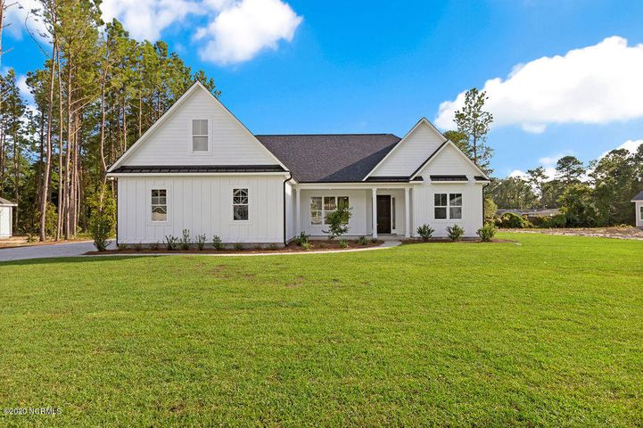 Sapphire plan features Board and Batten accented siding with metal accent roof, 4 bedrooms, 3 full bathrooms, bonus room & side load 2 car garage all on a 0.50 acre home site! Beautiful details inside and out.  As you enter the foyer, it opens up to a vaulted ceiling in the Great Room w/ custom trim package throughout. First you notice craftsman wainscoting going around the entire common area plus ship-lap from floor to ceiling and built-ins on both sides of the fireplace. Kitchen features Quartz countertops with island & bar sitting area, tile back-splash, under cabinet lighting, soft close doors and drawers and a beautiful farmhouse sink! Gas Range with custom wood cabinet hood above it. Dining/breakfast nook has tons of windows for plenty of natural light entering the Kitchen and living area. Telescoping doors give access to the screened in back porch overlooking this wooded private lot. Master Suite has a full tile shower with rain-head and wall mounted shower heads plus your walk in closet with custom wood shelving and niches. Laundry room/ mud room with a sink is standard. Upstairs is the bonus room, an additional  4th bedroom plus a full bathroom. Outside full sod on front, back & sides of the property plus gutters all the way around the home. Discover Crown Pointe and enjoy larger home sites with custom new homes within walking distance to the waterfront dock & gazebo. No flood zone, located in the Topsail School District. Crown Pointe is a waterfront community with winding streets, double sidewalks, new pool & clubhouse and best of all a waterfront dock & gazebo with kayak launch and day-dock.