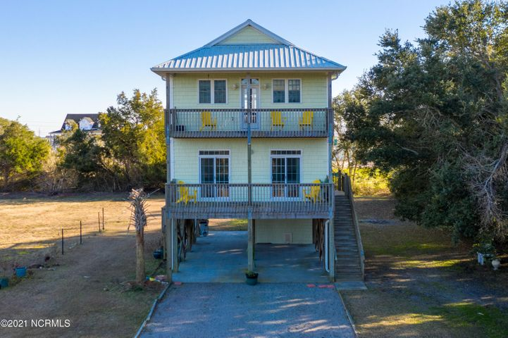 This Sneads Ferry home close to the ICW is ready to be moved in, rented out, or spent as a weekender! This coastal home has decks on each level with glimpses of the water. There is a private backyard with a tree line and all the space you need for furry friends! Minutes from the back gate to Camp Lejuene  base and minutes to Topsail Island! This location is very popular for boaters or beach lovers! The interior of the home boasts the the reverse flooring concept to magnify the island feel. Vaulted ceilings, open floor plan, with stainless steel kitchen appliances all add to the modern feel of this home. You will appreciate the exterior features such as a metal roof, easy maintenance high quality vinyl siding and a three vehicle carport. Perfect for all your outdoor toys or vehicles. And of course a storage building under the home for bikes are yard tools! This property will not last long, schedule your appointment for viewing today!